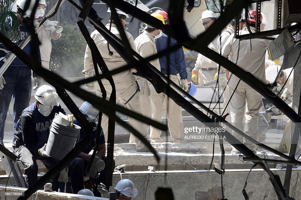 Mexican Navy members remain near the damaged building of Mexican state-owned oil giant Pemex, after a blast, in Mexico City on February 5, 2013. A gas build-up caused the explosion that rocked the headquarters of Mexico's state-owned oil firm last week, killing 37 people, officials said Monday, ruling out a bomb attack. The explosion also injured morfe than 120 people. AFP PHOTO/Alredo Estrella