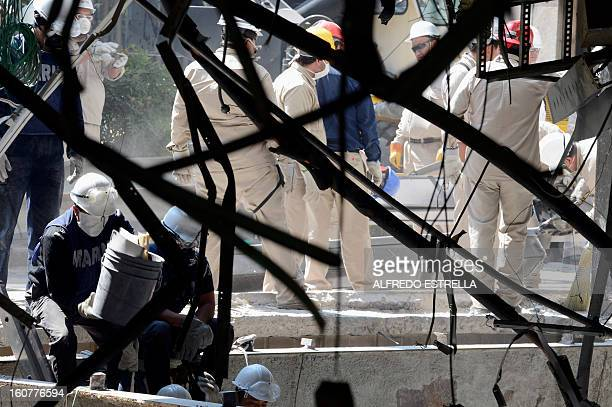 Mexican Navy members remain near the damaged building of Mexican stateowned oil giant Pemex after a blast in Mexico City on February 5 2013 A gas...