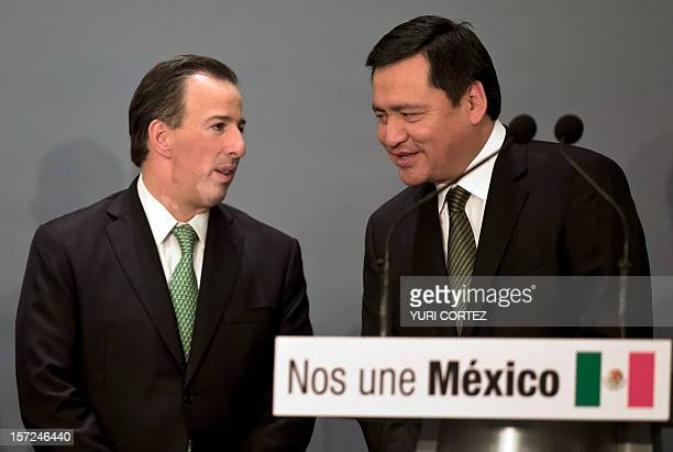 Mexican new Interior Secretary Miguel Angel Osorio Chong speaks with new Secretary of Foreign Affairs Jose Antonio Meade during a ceremony in which...