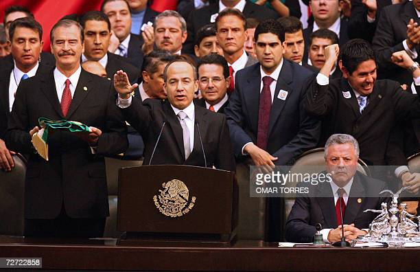 Mexican new President Felipe Calderon takes the presidential oath next to outgoing President Vicente Fox and the president of the Chamber of Deputies...