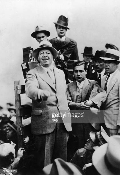 Mexican painter Diego Rivera dressed in a lightcolored suit and hat delivers an impassioned speech from a crowded podium 1930s