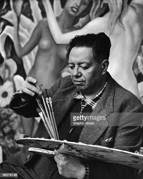 Mexican painter Diego Rivera selects a brush from his palette while he works on a mural 1948