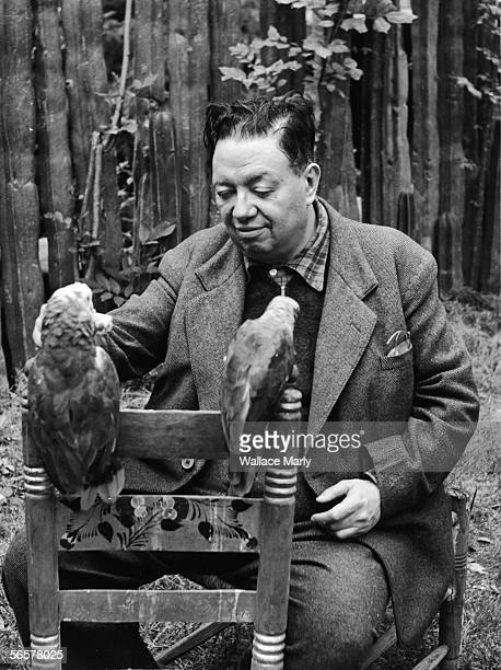 Mexican painter Diego Rivera sits outside and feeds a pair of parrots perched on the back of a painted chair 1940s