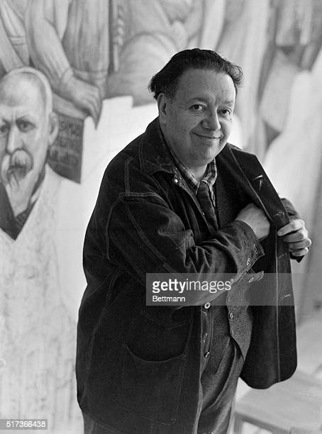 Mexican painter Diego Rivera smiles as he reaches into his coat