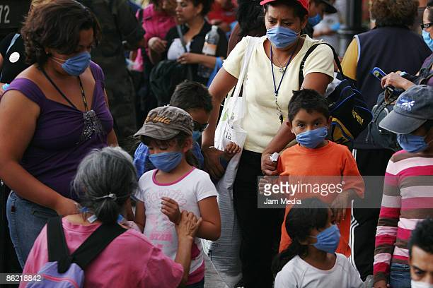 Mexican people wear face masks on the street as prevention against the swine flu virus on April 25 2009 in Mexico City Mexico An outbreak of deadly...