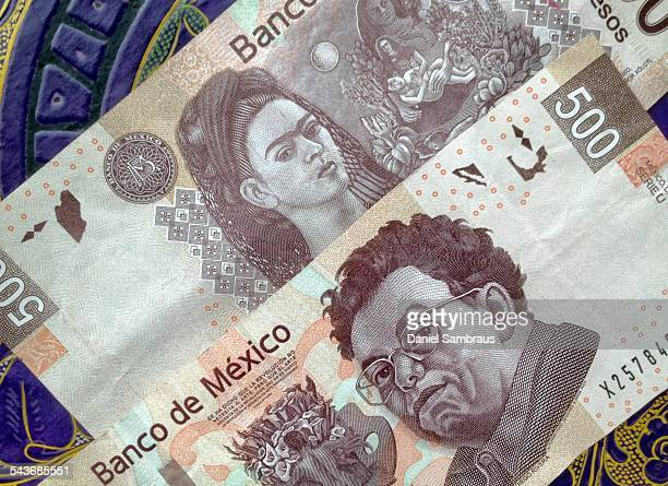 500 Mexican pesos notes on a table with traditional Mexican ornament The note has the portrait of the painter Diego Riviera on one side and Frida...