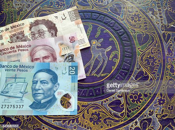 Mexican pesos notes on a table with traditional Mexican ornament The 500 pesos note has the portrait of the painter Diego Riviera V 20 is all...