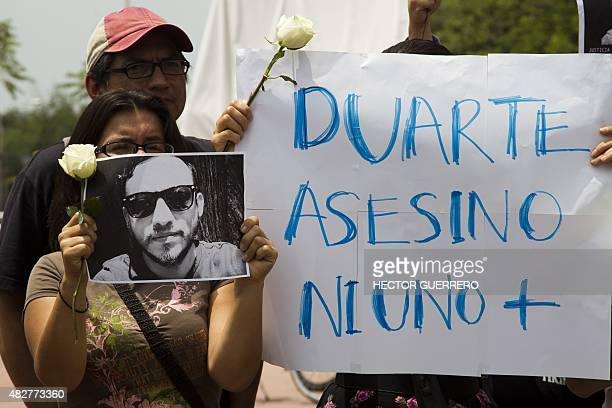 """Mexican photojournalists hold a picture of murdered colleague Ruben Espinosa and a banner reading """"Duarte assassin. Not one more"""" --for Javier..."""