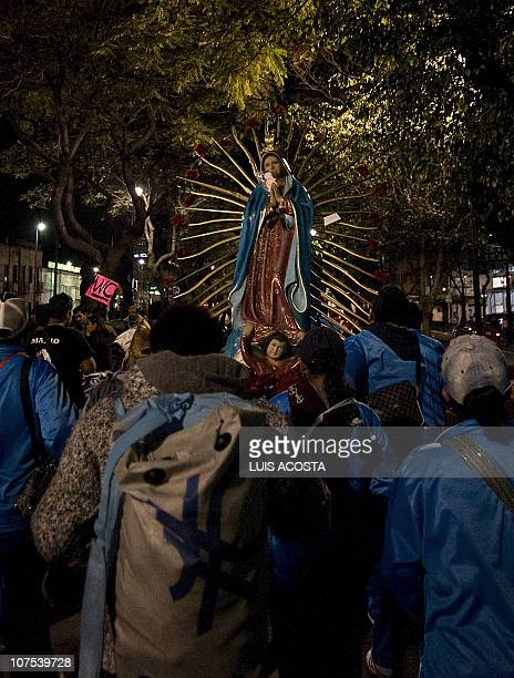 Mexican pilgrims carry an image of Our Lady of Guadalupe Mexico's patron saint while heading to the Basilica of Guadalupe in Mexico City during the...