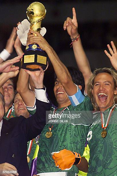 Mexican players Claudio Suarez and Luis Hernandez lift the 1999 Confederations Cup championship trophy after winning the tournament by defeating...
