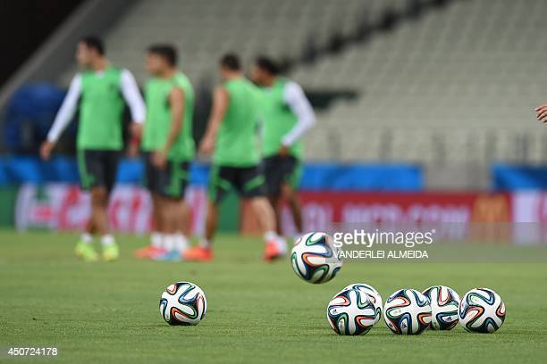 Mexican players warm up next to official Brazuca balls during a training session at the Castelao Stadium in Fortaleza on June 16 on the eve of a FIFA...
