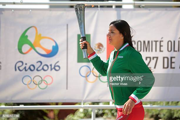 Mexican pole vaulter Carmen Correa runs with an Olympic torch during a ceremony to stand out the 100 Days to Rio 2016 Olympic Games at Centro...