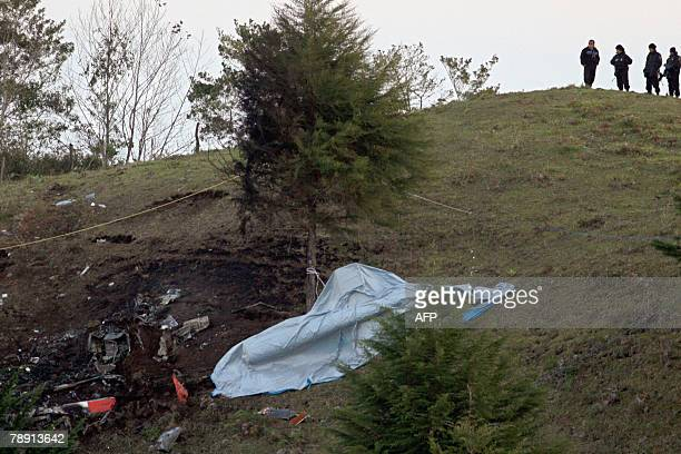 Mexican police members look at the remains of a helicopter crashed on Tepango de Rodriguez community in Puebla State Mexico 11 January 2008 The...