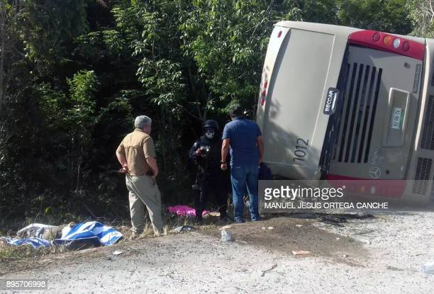 Mexican police officers and paramedics work in the scene of a road accident where a bus driving tourists to Chacchoben archaeological zone overturned...