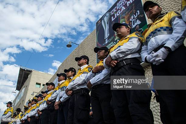Mexican police officers stand guard outside the Mexican television network Televisa headquarters as demonstrators and relatives of the 43 missing...