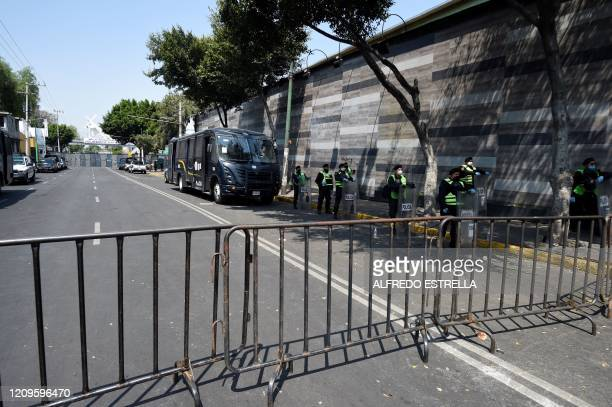 Mexican police stand behind protective fences to prevent faithfuls from passing during the representation of the Passion of Christ on Good Friday in...
