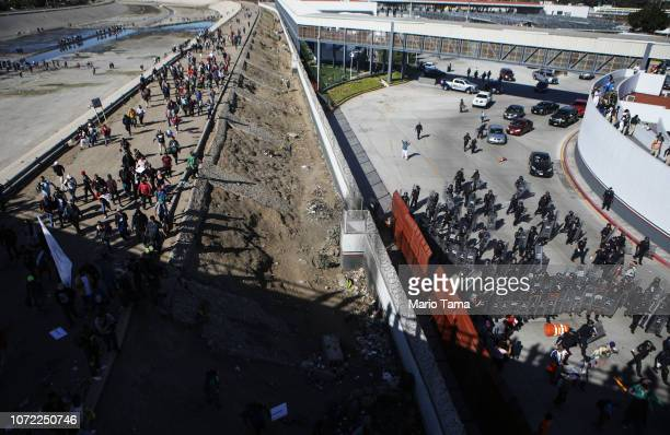 Mexican police stand guard as migrants walk on a bank of the nearly dry Tijuana River as they make their way toward the El Chaparral port of entry...