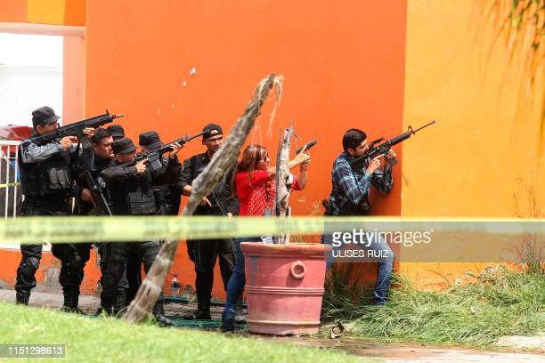 Mexican Police take position outside a house searching for armed men involved in a shooting in another house of a gated community in Tlajomulco de...