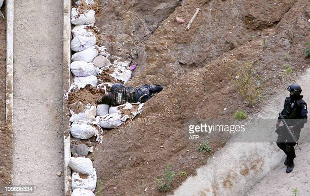 A Mexican policeman patrols near the corpse of colleague after a bus was burnt during an attack to a convoy of the police in Zitacuaro Michoacan...