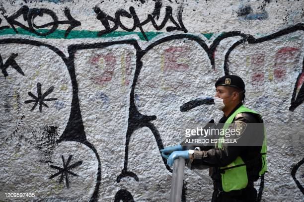 A Mexican policeman stands guard while preventing faithfuls from passing during the representation of the Passion of Christ on Good Friday in the...