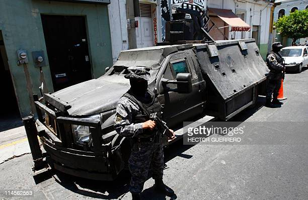 "Mexican policemen stand guard next to an armoured car seized to alleged members of the Mexican drug cartel ""Los Zetas"" and presented to the press on..."