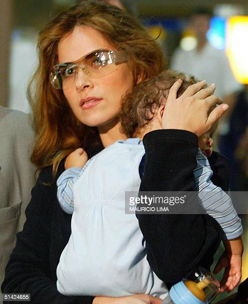 Mexican pop star Gloria Trevi with her 10monthold son Angel Gabriel in her arms is being escorted by Brazilian Federal Police officers five hours...