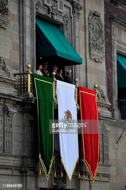 Mexican President Andres Manuel Lopez Obrador looks at a parade commemorating the 109th anniversary of the Mexican Revolution from a balcony of the...