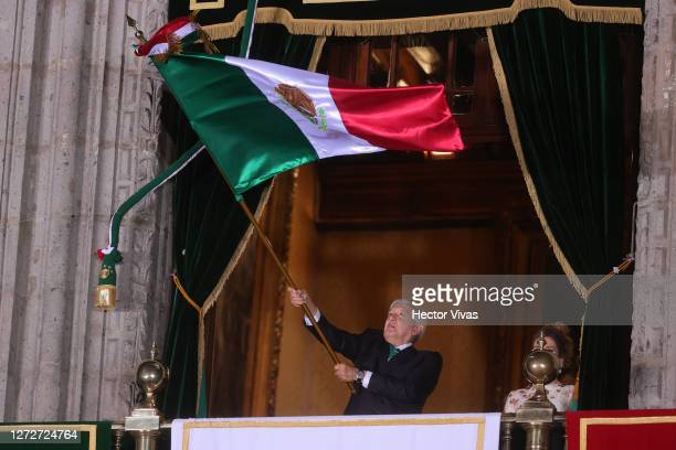 Mexican President Andres Manuel Lopez Obrador waves a Mexican flag as he gives the annual independence shout from the balcony of the National Palace...