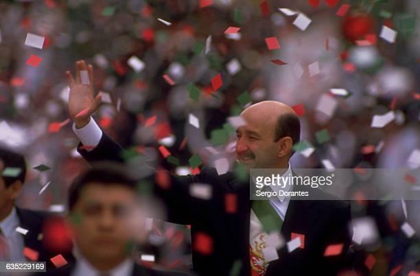 Mexican President Carlos Salinas de Gortari waves from his motorcade during a parade in Mexico City