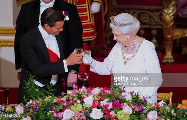 Mexican President Enrique Pena Nieto and Britain's Queen Elizabeth II make a toast during a state banquet at Buckingham Palace in London on March 3...
