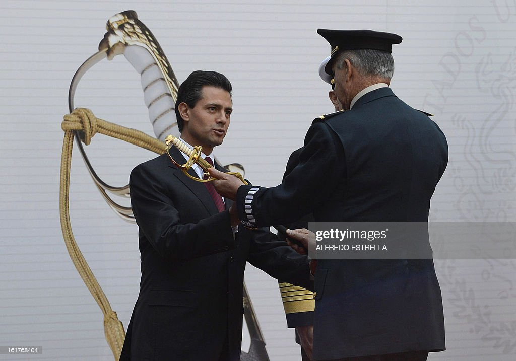 Mexican President Enrique Pena Nieto (L) and Defence Secretary General Salvador Cienfuegos take part in the ceremony known as the 'Delivery of the Sword and Sabre to the President of Mexico and Supreme Commander of the Armed Forces', at the National Palace in Mexico City, on February 15, 2013. AFP PHOTO/Alfredo ESTRELLA
