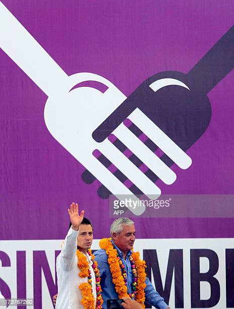 Mexican President Enrique Pena Nieto and Guatemalan President Otto Perez Molina wave during an event within the National Crusade against Hunger...