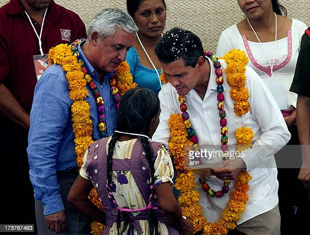 Mexican President Enrique Pena Nieto and Guatemalan President Otto Perez Molina speak with an indigenous woman during an event within the National...