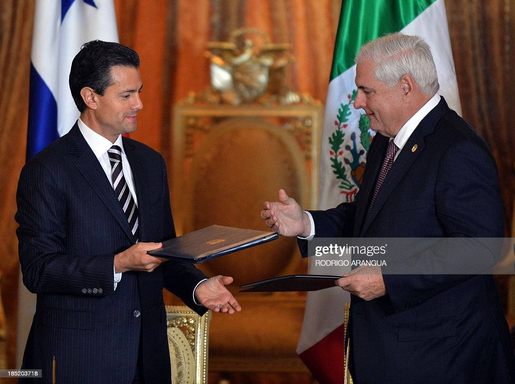 Mexican President Enrique Pena Nieto (L) and his Panamanian counterpart Ricardo Martinelli exchange documents after the signature of bilateral agreements at Las Garzas Presidential Palace in Panama City on October 18, 2013, in the framework of the XXIII Ibero-American Summit. AFP PHOTO / Rodrigo ARANGUA