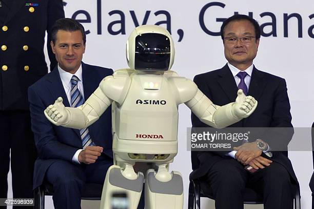 Mexican President Enrique Pena Nieto and Japanese Honda CEO Takanobu Ito watch the presentation of robot Asimo during the opening of the new Honda...