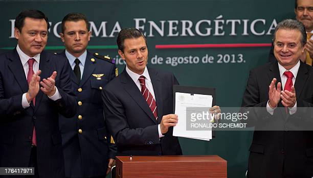 Mexican President Enrique Pena Nieto next to Energy Secretary Pedro Joaquin Coldwell and Mexican Interior Minister Miguel Osorio Chong shows the bill...