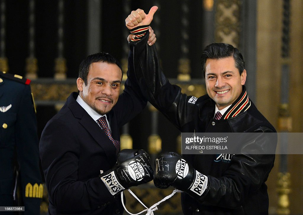 Mexican President Enrique Pena Nieto (R) poses with Mexican boxer Juan Manuel Marquez (L), welterweight champion, at the Palacio Nacional, in Mexico City, on December 14, 2012. AFP PHOTO/Alfredo Estrella