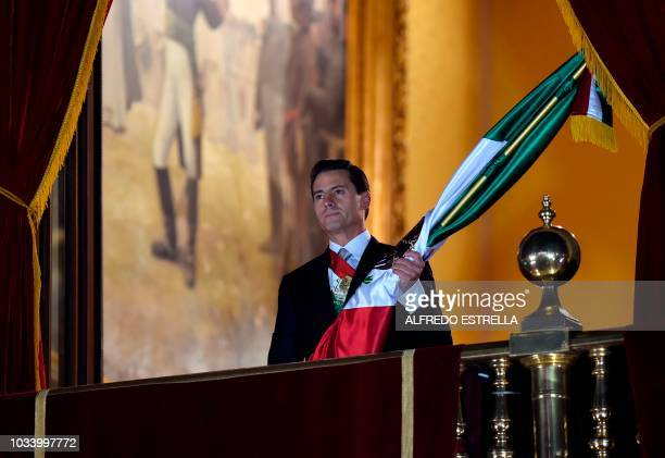 Mexican President Enrique Pena Nieto prepares to wave the Mexican National Flag on the main balcony of the National Palace during ceremonies called...