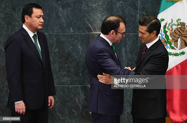 Mexican President Enrique Pena Nieto shake hands with resigning Secretary of Finance Luis Videgaray as Interior Minister Miguel Angel Osorio Chong...