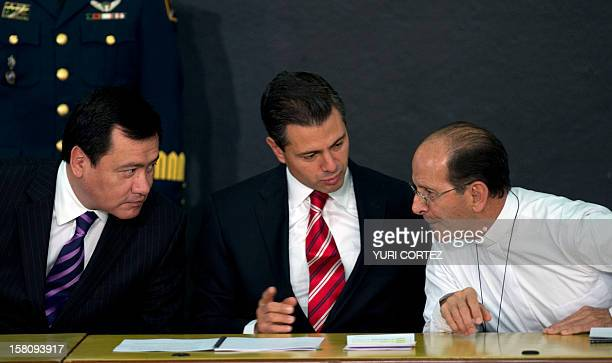 Mexican President Enrique Pena Nieto speaks to Mexican Catholic priest Alejandro Solalinde next to Mexican Interior Minister Miguel Angel Chong...