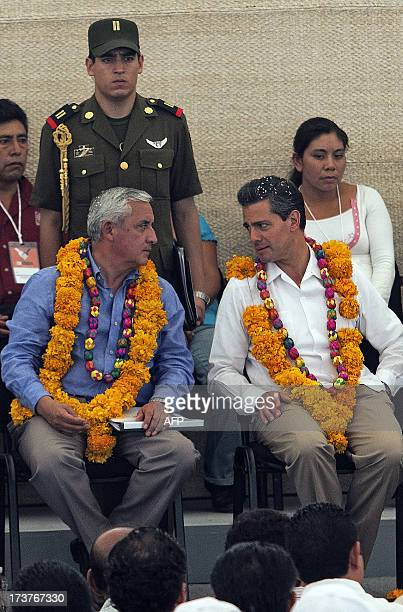 Mexican President Enrique Pena Nieto speaks with Guatemalan President Otto Perez Molina during an event within the National Crusade against Hunger...