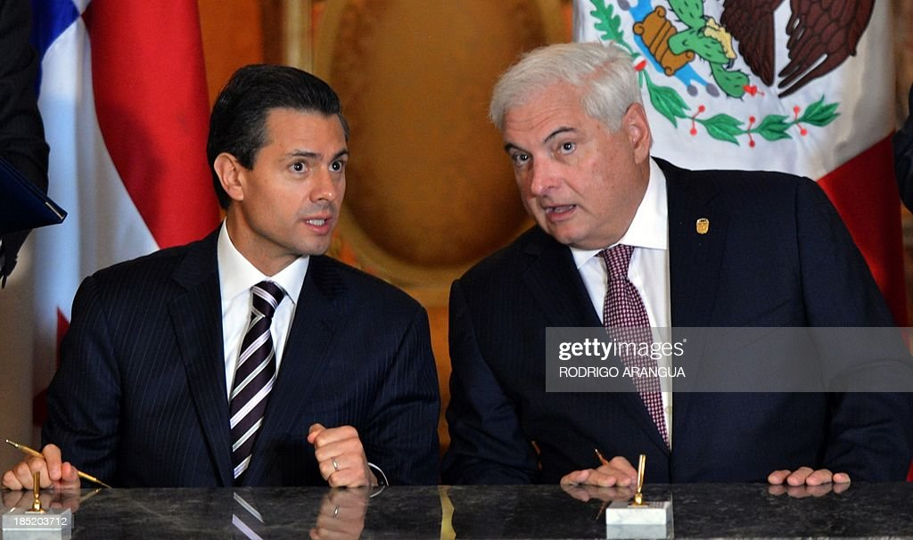 Mexican President Enrique Pena Nieto (L) speaks with his Panamanian counterpart Ricardo Martinelli at the Las Garzas Presidential Palace in Panama City on October 18, 2013, before signing bilateral agreements in the framework of the XXIII Ibero-American Summit. AFP PHOTO / Rodrigo ARANGUA