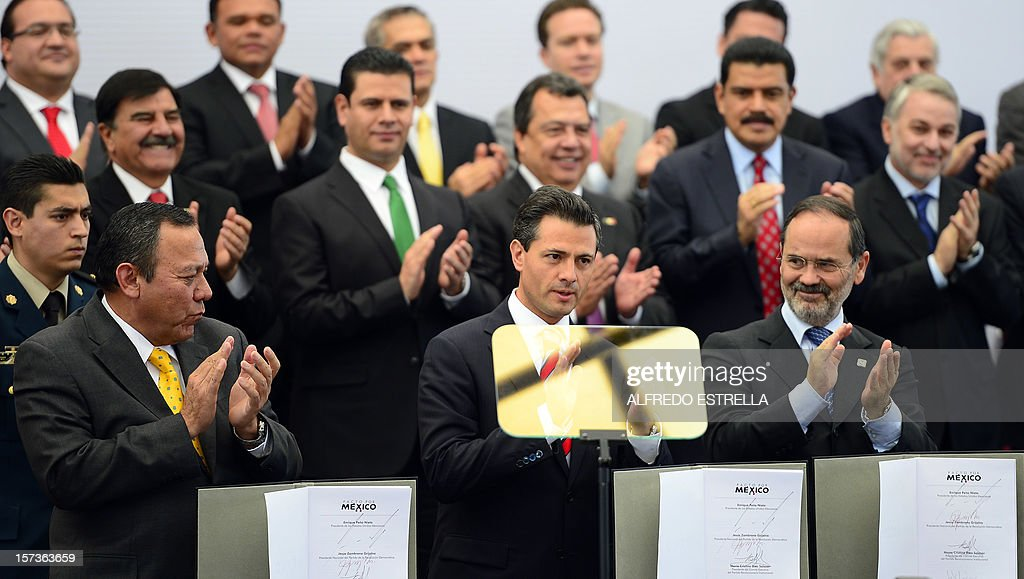 Mexican President Enrique Pena Nieto (C, bottom row), the President of the Democratic Revolution Party (PRD), Jesus Zambrano (L, bottom row), and the President of the National Action Party (PAN), Gustavo Madero (R, bottom row), applaud as they make the 'Pact for Mexico', on December 2, 2012 in Mexico City. Pena Nieto and the main three polical parties of Mexico, signed Sunday an agreement to launch reforms to strengthen democracy, fight social inequality and promote economical growth. AFP PHOTO/Alfredo Estrella