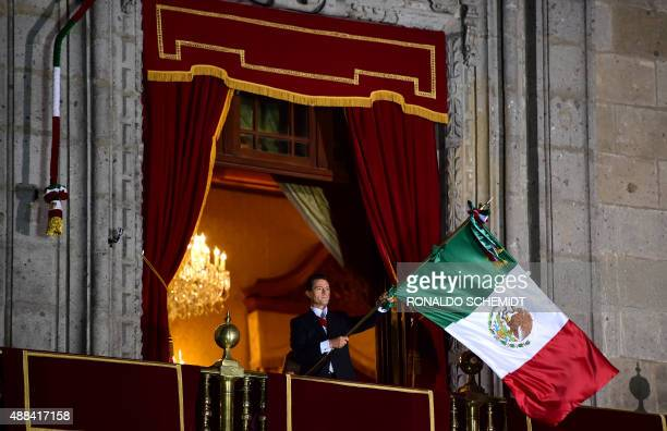 Mexican President Enrique Pena Nieto waves the Mexican National Flag on the main balcony of the National Palace during ceremonies called The Shout...