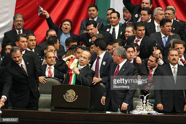 Mexican President Felipe Calderon center puts on his sash during his inauguration with former President Vicente Fox left at Mexico's Congress in...