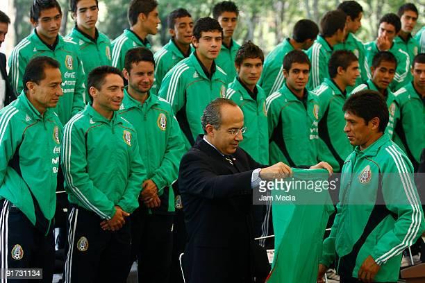 Mexican President Felipe Calderon Hinojosa receives a shirt from Jose Luis Gonzalez headcoach of the Mexican U17 National Soccer Team during their...