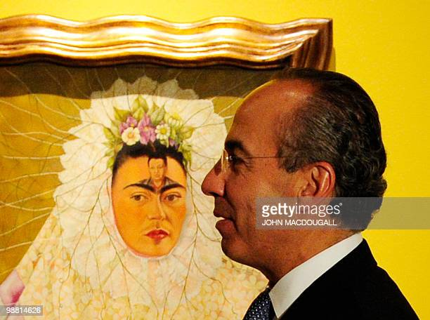 Mexican President Felipe Calderon poses in front of Mexican artist Frida Kahlo's 'SelfPortrait as Tehuana or Diego on my Mind' as he visited a major...