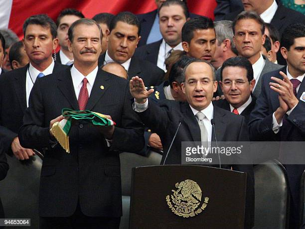 Mexican President Felipe Calderon right takes the oath of office with former President Vicente Fox left at Mexico's Congress in Mexico City Friday...