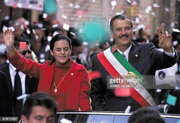 Mexican President Vicente Fox along with his daughter Ana Cristina waves to the crowd as they travel by car 01 December through Mexico City to the...
