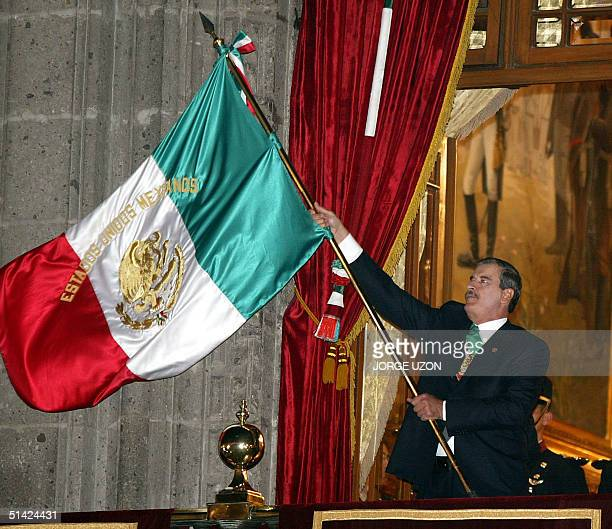 Mexican President Vicente Fox waves the Mexican flag on the balcony of the presidential palace during the celebration of 192nd anniversary of Mexican...